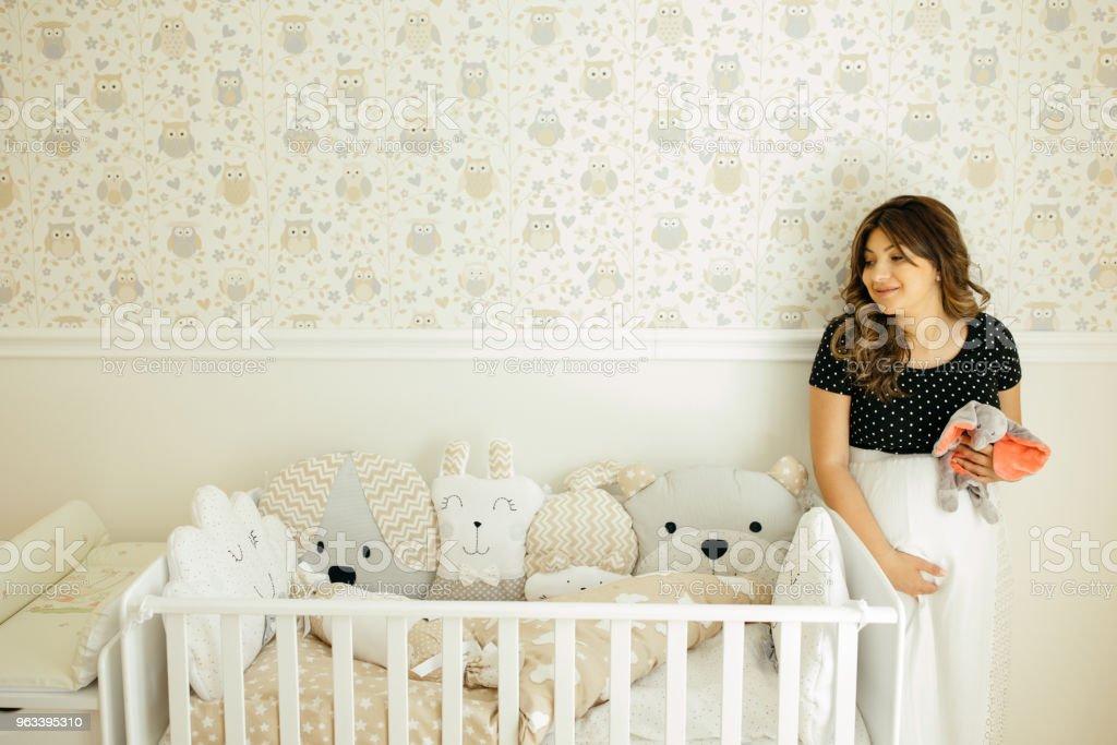 Pregnant woman near the crib