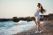 A young pregnant woman, brunette, long straight hair, sunglasses and straw hat by the sea.Outdoors portrait of beautiful young pregnant woman on blue ocean background alone.Summer portrait of a pregnant woman near the sea