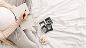 Preparing for childbirth. Pregnant woman noting noting down thoughts, top view, empty space