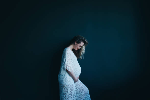 Pregnant woman on a dark background. stock photo