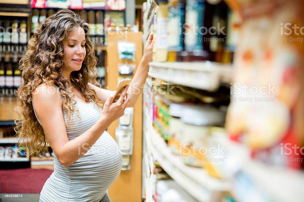 Schwangere Frau am Telefon im Supermarkt – Foto