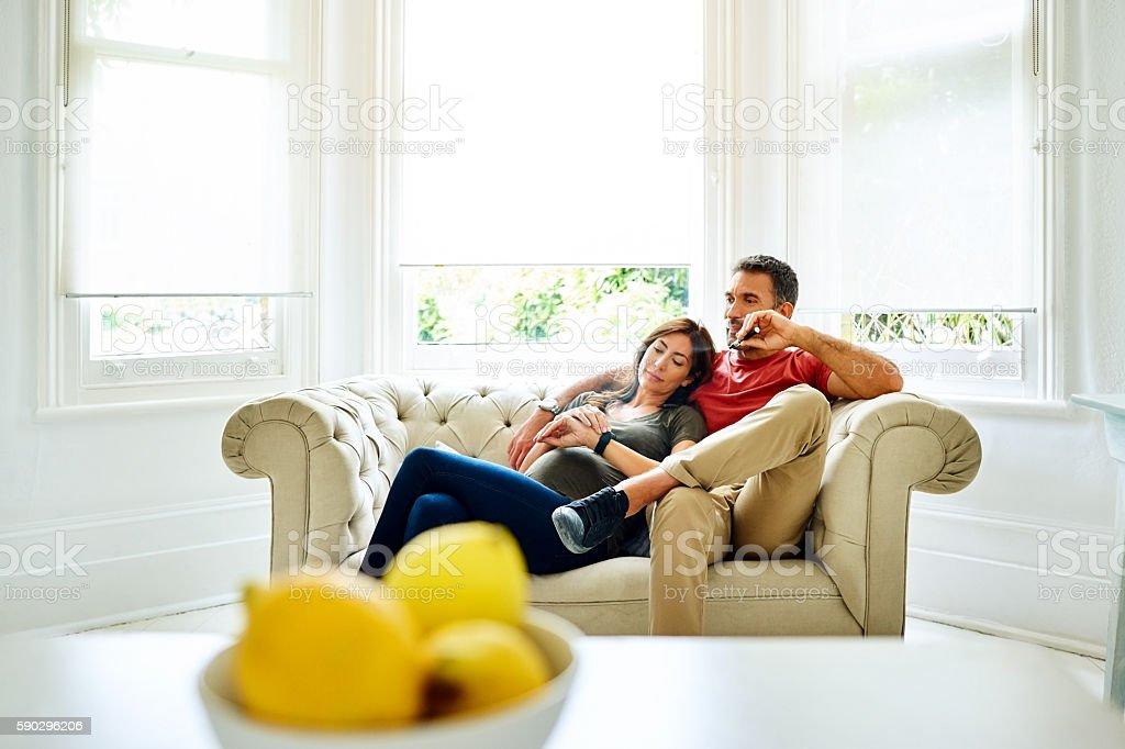Pregnant woman on sofa with husband smoking e-cigarette royaltyfri bildbanksbilder