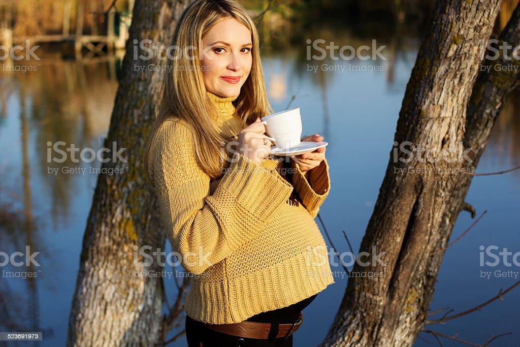 Pregnant woman on the autumn lake stock photo