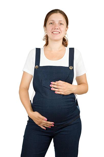schwangere frau in weiß - latzhose für schwangere stock-fotos und bilder