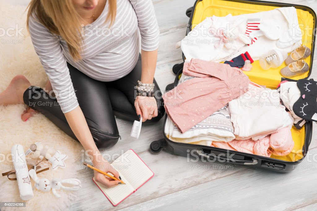 Pregnant woman packing for hospital and taking notes стоковое фото