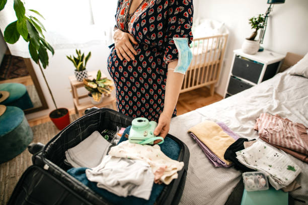 Pregnant woman packing stuff for maternity hospital stock photo