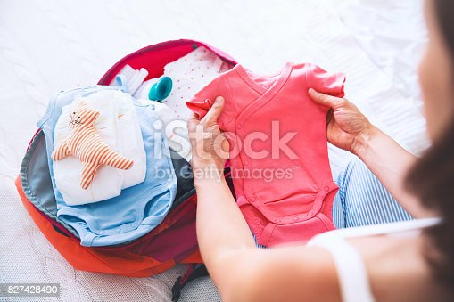 istock Pregnant woman packing suitcase, bag for maternity hospital at home, getting ready for newborn birth, labor. 827428490