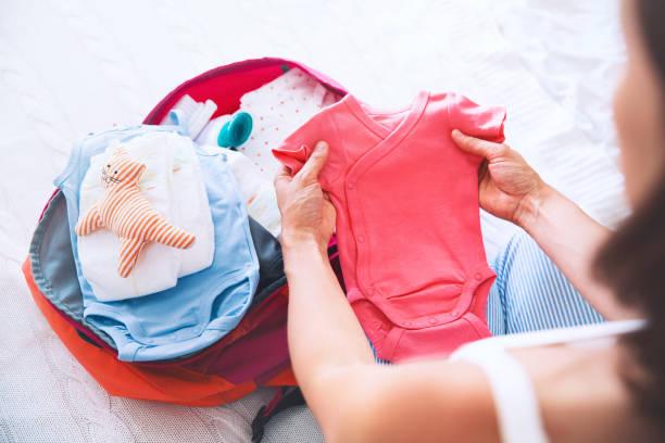 Mujer embarazada embalaje maleta de viaje, bolsa de maternidad en casa, preparándose para el nacimiento de recién nacido, mano de obra. - foto de stock