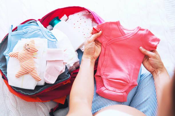 schwangere frau packen koffer, tasche für geburtsklinik zu hause, immer bereit für neugeborene geburt, arbeit. - babytasche stock-fotos und bilder