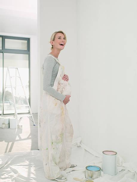 schwangere frau painting kinderzimmer - latzhose für schwangere stock-fotos und bilder