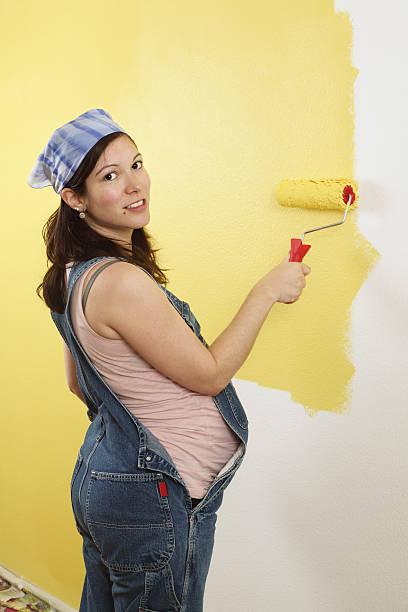 schwangere frau painting - latzhose für schwangere stock-fotos und bilder