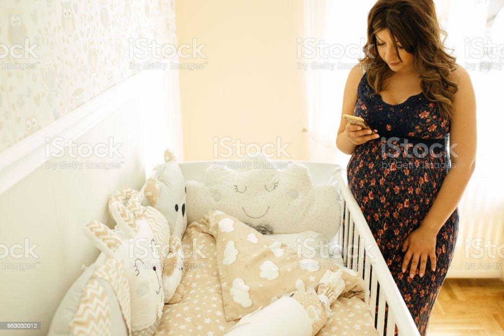 Pregnant woman photographing crib