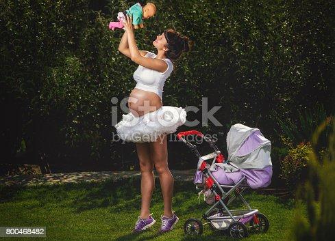 Beautiful pregnant woman having fun in garden