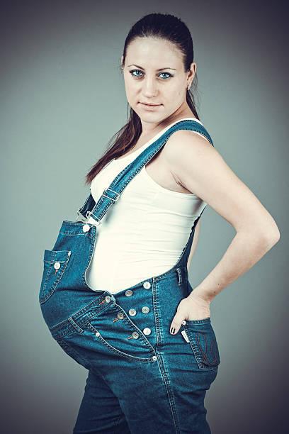 schwangere frau posieren auf grauem hintergrund. - latzhose für schwangere stock-fotos und bilder