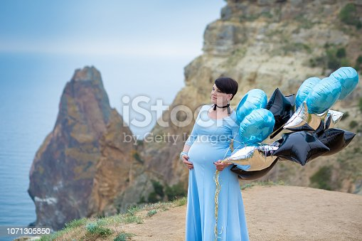 istock Pregnant woman posing on mountain coast line wearing blue long dress with air baloons. 1071305850