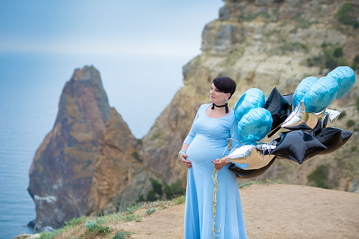 1071305850 istock photo Pregnant woman posing on mountain coast line wearing blue long dress with air baloons. 1071305850