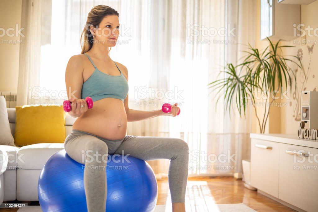 Pregnant woman practicing yoga and fitness at home.
