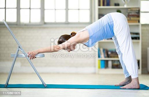 Pregnant woman practicing yoga at home - adho mukha svanasana pose