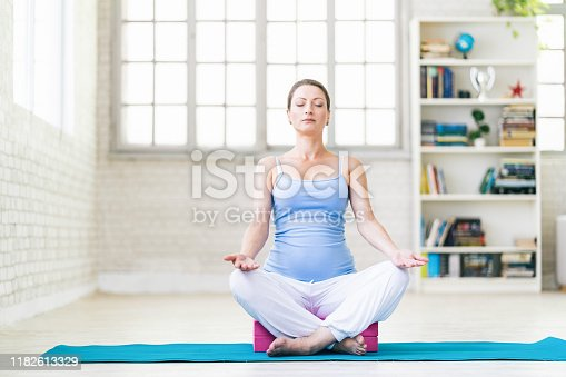 511849865 istock photo Pregnant woman practicing yoga at home 1182613329