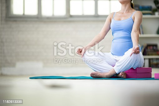 511849865 istock photo Pregnant woman practicing yoga at home 1182613335