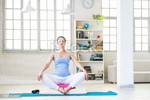 511849865 istock photo Pregnant woman practicing yoga at home 1201604652