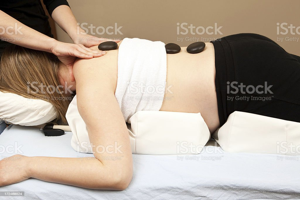 Pregnant Woman Prenatal Massage with Hot Stones and Bolster stock photo