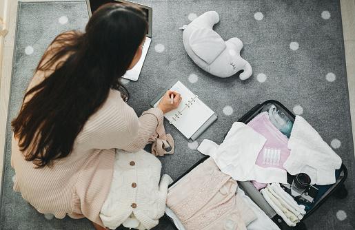 A pregnant woman prepares a bag for the hospital