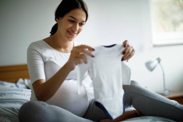 出産の準備をしている妊婦 - 乳児用衣類 ストックフォトと画像