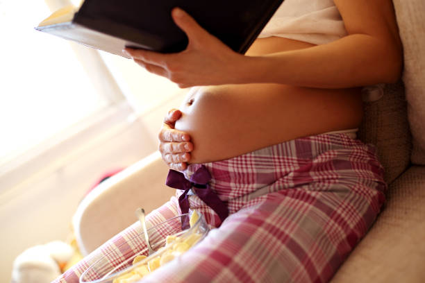 Pregnant woman reading book for her baby stock photo