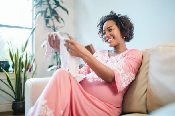 mujer embarazada recibe ropa infantil en baby shower - baby shower fotografías e imágenes de stock