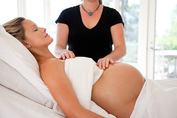 pregnant woman receives prenatal massage and reiki energy work - midwife stock pictures, royalty-free photos & images