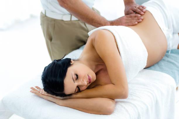 schwangere frauen erhalten eine rückenmassage masseur - chiropraktik wellness stock-fotos und bilder