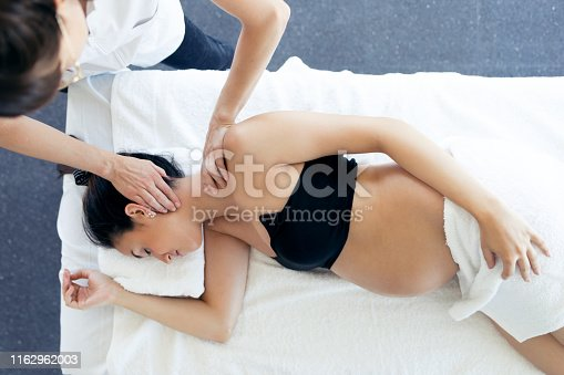 609830806 istock photo Pregnant woman receiving osteopathic or chiropractic treatment in neck in a clinic. 1162962003