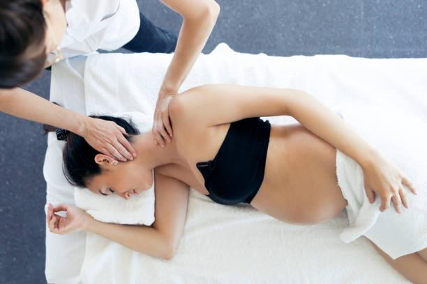 Schwangere Frau, die in einer Klinik eine osteopathische oder chiropraktische Behandlung im Nacken erhält. – Foto
