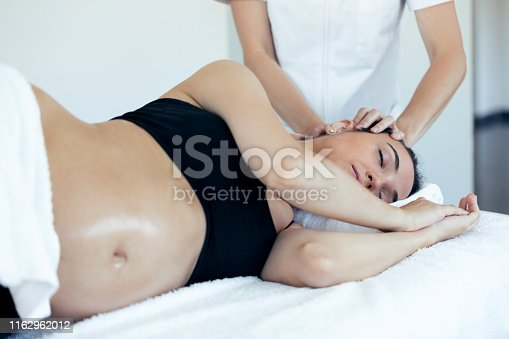 609830806 istock photo Pregnant woman receiving osteopathic or chiropractic treatment in neck in a clinic. 1162962012