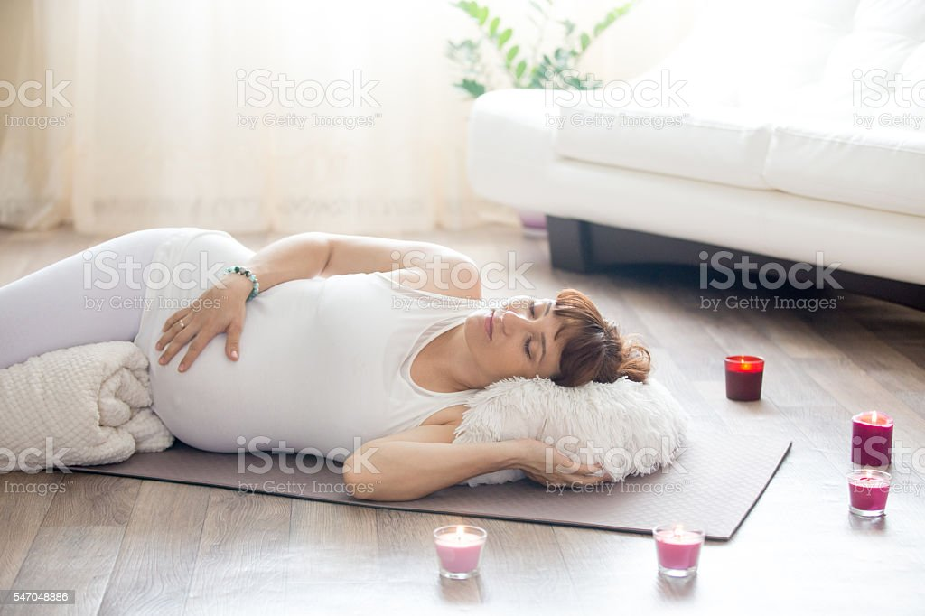 Pregnant woman relaxing after yoga practice in corpse pose stock photo