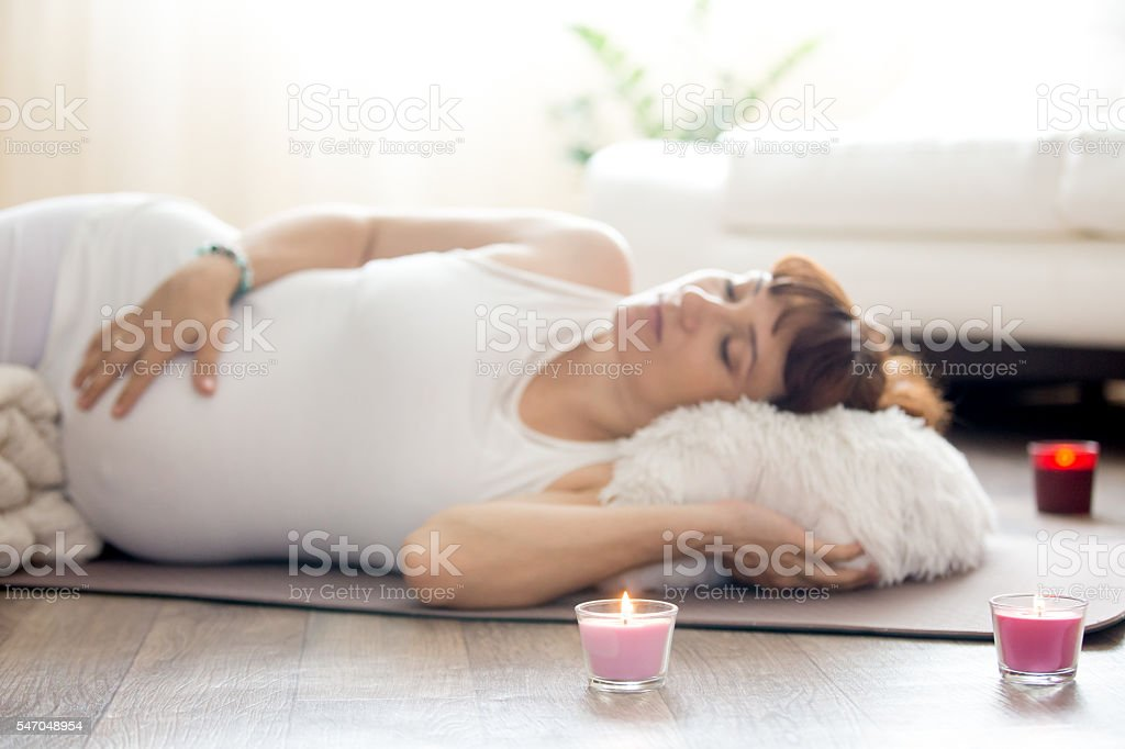 Pregnant woman relaxing after yoga practice in Shavasana pose stock photo