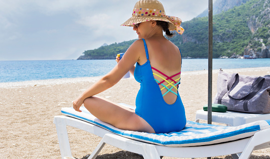 1071305850 istock photo Pregnant woman relaxing on the beach 998453058