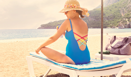 1071305850 istock photo Pregnant woman relaxing on the beach 999848508