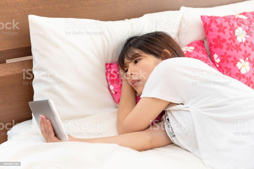 Gravid kvinna att se tablett i sängen - Royaltyfri 20-29 år Bildbanksbilder