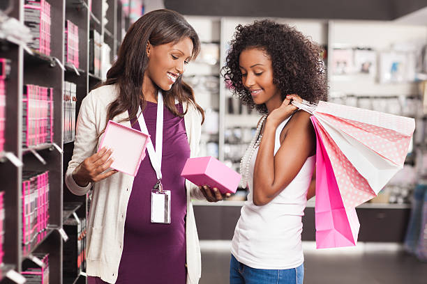 pregnant woman seller at beauty store. - makeup for pregnant women stock photos and pictures
