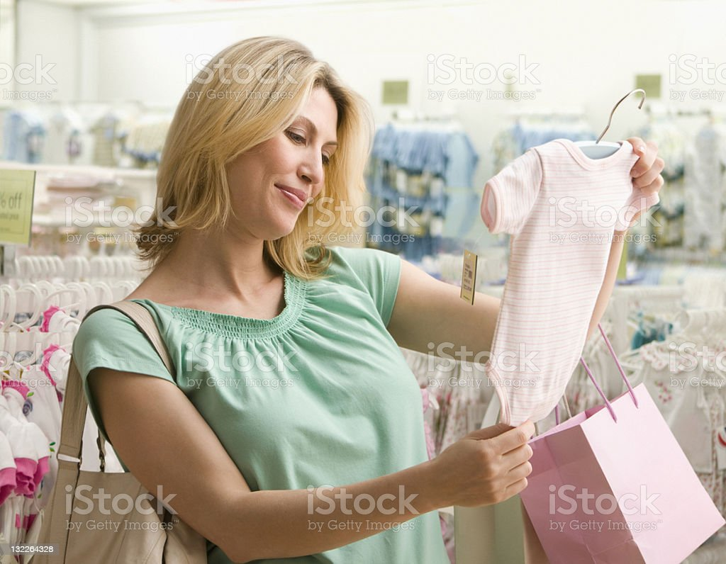 Pregnant woman shopping for baby clothes stock photo