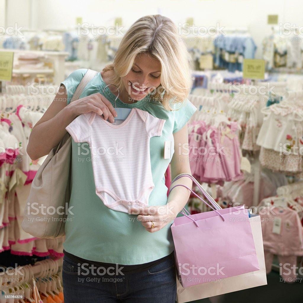 Schwangere Frau shopping für Kleidung für Babys – Foto