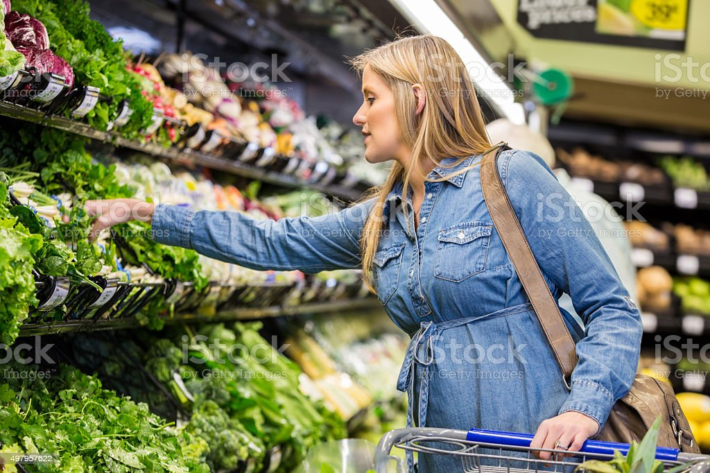 Pregnant woman shopping for healthy food in supermarket Mid adult Caucasian pregnant woman is shopping for fresh vegetables and healthy food in local grocery store or supermarket. Expecting mother is pushing a shopping cart and reaching to select lettuce from cooler in produce section. 2015 Stock Photo