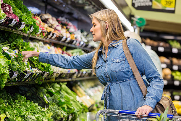 Pregnant woman shopping for healthy food in supermarket Mid adult Caucasian pregnant woman is shopping for fresh vegetables and healthy food in local grocery store or supermarket. Expecting mother is pushing a shopping cart and reaching to select lettuce from cooler in produce section. romaine lettuce stock pictures, royalty-free photos & images
