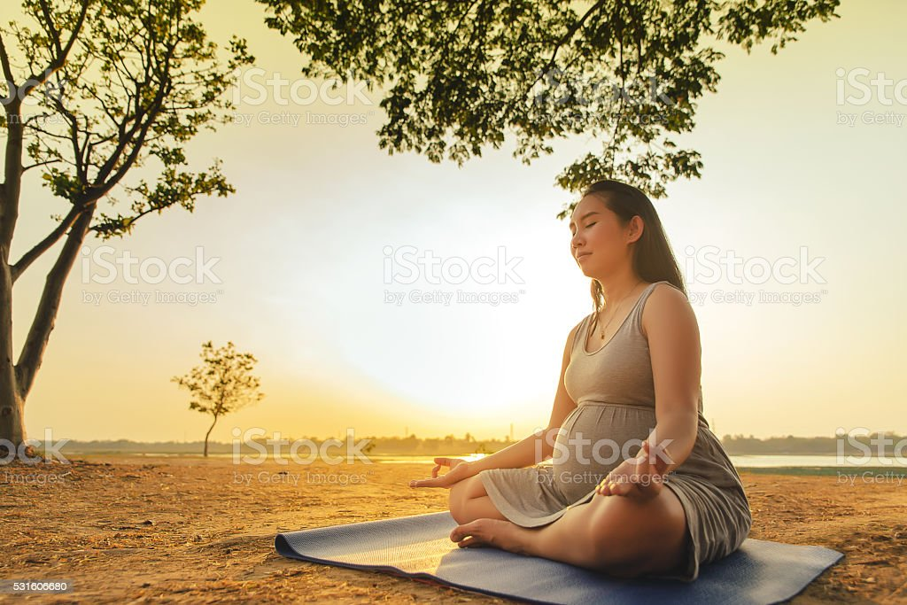 Pregnant woman silhouette yoga is sunset stock photo