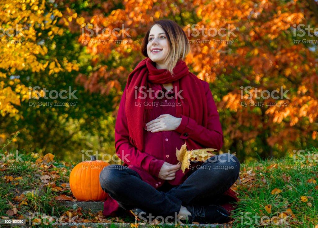 pregnant woman sitting at ground in autumn season time stock photo