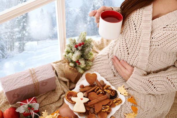 la mujer embarazada sentada cerca de la ventana y bebiendo el té, paisaje hermoso del invierno con el bosque nevado está fuera de la ventana, decoración de la Navidad - foto de stock