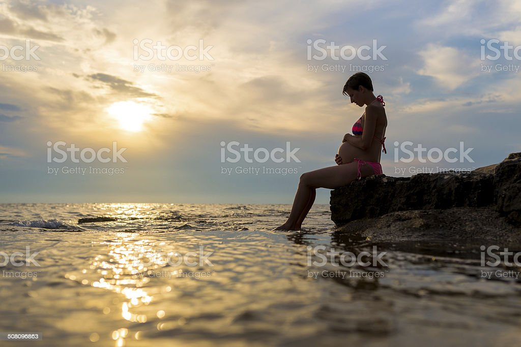 Pregnant woman sitting on a rock by the sea stock photo