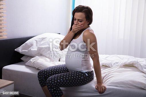 Side View Of A Young Woman Sitting On Bed In Bedroom